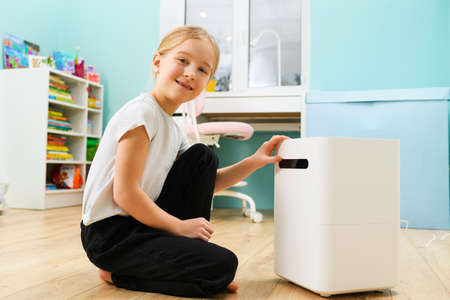 Primary school age blonde girl enjoy comfort at home with air humidifier white box, health care and modern devices