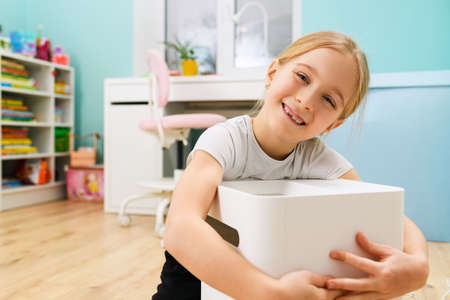 Charming female child portrait with air humidifier at room interior, device for health and comfortable home staying
