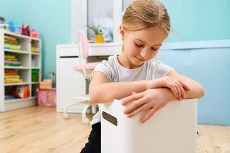 School girl put hands of big white air humidifier device at child light room, health care during isolation 스톡 콘텐츠