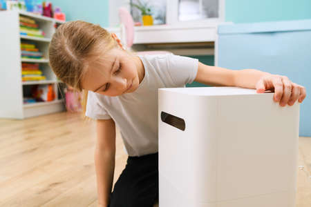 Small girl sitting at room floor and looking at big air humidifier device close up for comfort home staying Imagens