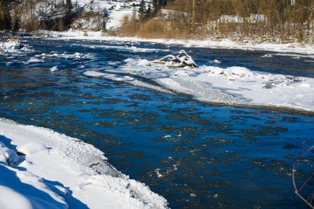 Frost, ice and snow at narrow water stream of mountain river at forest, nature landscape of Carpathians, Ukraine