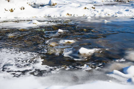Mountain river water shallow surface with stones, ice and snow, nature landscape of Carpathian mountains, Ukraine 스톡 콘텐츠