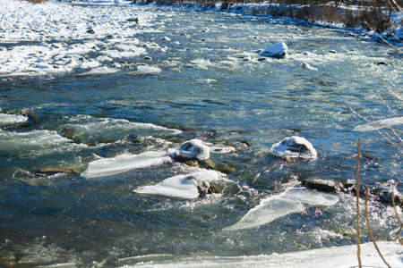 Texture of frozen river stream and stones covered with ice and snow at sunny day, nature landscape of Carpathian mountains, Ukraine