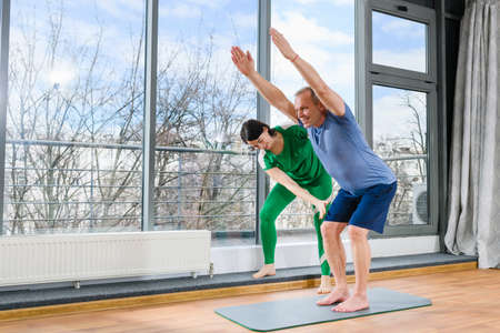 Senior man with young female osteopath during therapeutic gymnastics workout at light studio, training for knees with hands raising up