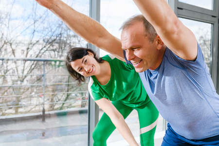 Positive aged man with hands up making wellness training workout with female doctor osteopath indoors, healthy lifestyle Imagens