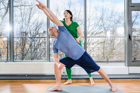 Middle age man stay on mat in light hall with panoramic window and exercise with female doctor, therapeutic gymnastics, health rehabilitation