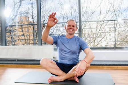Positive sportive middle age man sit on floor mat and show okay gesture in light studio, healthy lifestyle