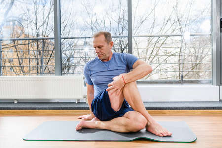 Middle age sportive man during workout training on floor mat in light studio, twirl and stretch body muscles Imagens