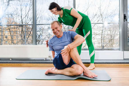Middle age man doing sport exercises, twirl body muscles with osteopath, therapeutic gymnastics and rehabilitation