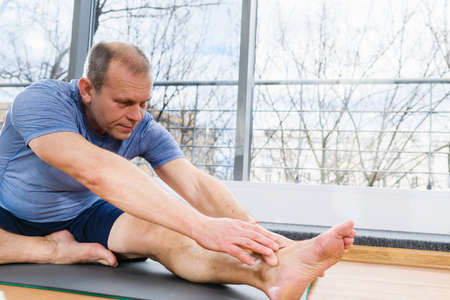 Middle age fit man sit on floor mat in light studio and stretch hands and feet, yoga fitness workout exercises