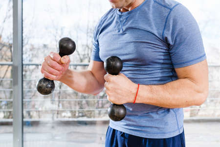 Sportive man torso in blue tight t-shirt with small dumbbells and red thread at light studio window background