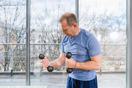 Middle age sportive fit smiling man in blue shirt workout with dumbbells in light gym with panoramic window