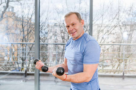 Middle age sportive fit smiling man in blue shirt workout with dumbbells in light gym with panoramic window. The man looks into the camera. Imagens