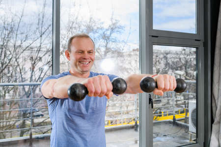 Smiling middle age fit sportsman exercise at light gym with panoramic window with weights, hands muscles training workout