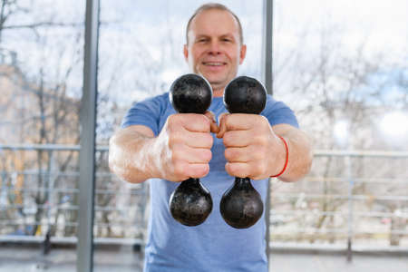 Fit aged smiling man hold two dumbbells close to camera near light gym window, healthy livestyle, workout, muscles training