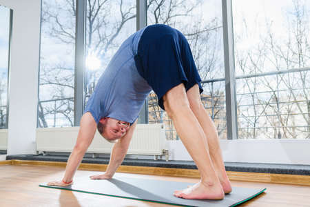 MIddle age man stay on floor mat, making workout yoga training in downward dog pose, tild and bend body muscles at light fitness studio Imagens