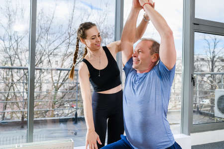 Middle age man make stretching workout exercises on mat in light fitness studio with panoramic window and female instructor assistance. Warrior pose with arms raised. Imagens