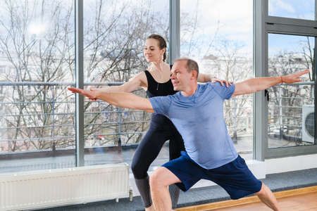 Mature aged man exercise workout balance with assistance of young female sport gym instructor near window in light fitness studio. Warrior pose.