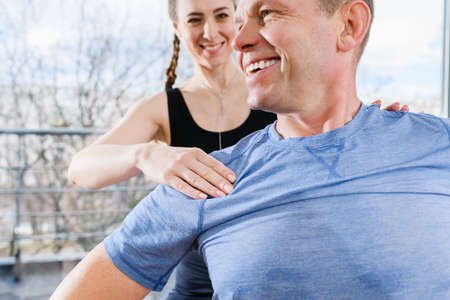 Middle age smiling fit man sit in gym and young instructor massaging, warming up body muscles before training exercises Imagens
