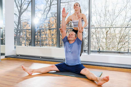 Middle age smiling man at yoga workout training with female instructor assistance, sit on mat with straight legs and hands up Imagens