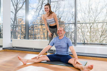 Happy young female trainer and mature man exercise training on mat in light hall with panoramic window Imagens
