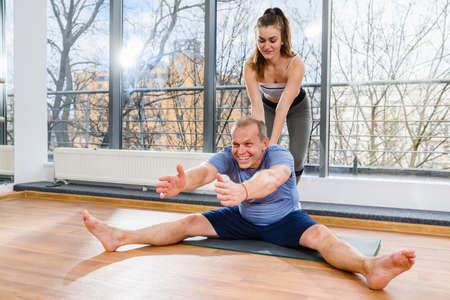 Positive fit aged man exercise workout at fitness club with young female instructor assistance on mat near panoramic window