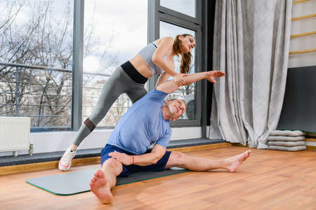 Aged man workout exercise stretching with female instructor assistance, bend on sides, warming up at light fitness club