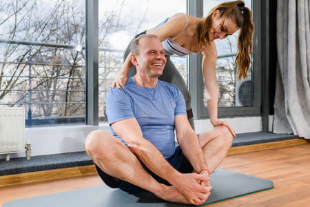 Smiling people exercise workout yoga lotus pose, stretching and warming up at light fitness studio, healthy lifestyle