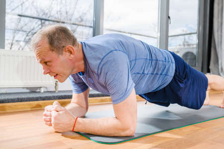 Aged fit sportsman stand in plank yoga fitness pose on floor mat in room, face close up, healthy lifestyle. Close-up. Imagens