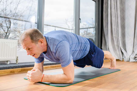 Aged fit sportsman stand in plank yoga fitness pose on floor mat in room, face close up, healthy lifestyle