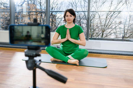 Female fitness trainer in green sportswear sit at mat in lotus pose with namaste gesture to start remote yoga exercise workout training