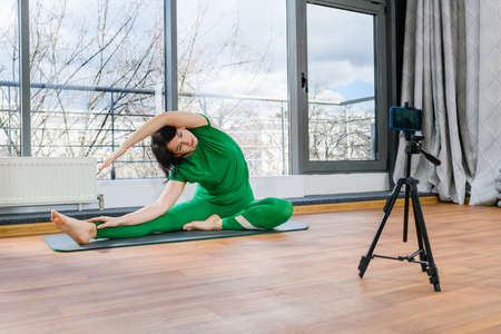 Female trainer in green sportswear exercise yoga fitness at online class, recording video lessons of workout training indoors
