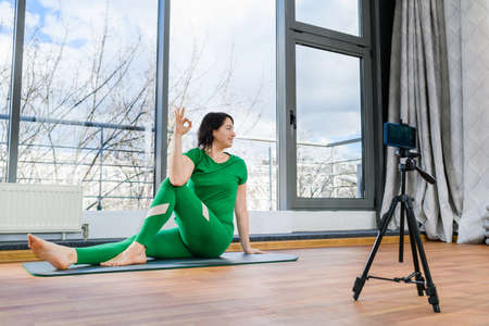 Female coach in green sportswear making online tutorial, master class of yoga, fitness training with mobile phone on tripod at light studio