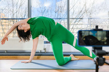 Woman in green sportswear make side slopes for smartphone camera recording on tripod, online remote fitness yoga class Imagens