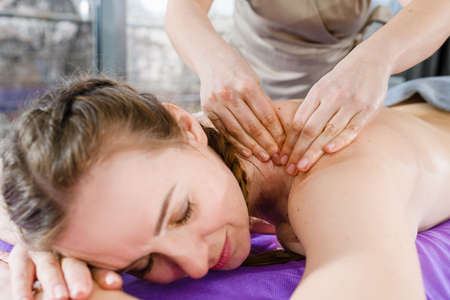 Young woman relax on massage session at spa fitness salon while masseur hands warm up her neck and back skin, body treatment