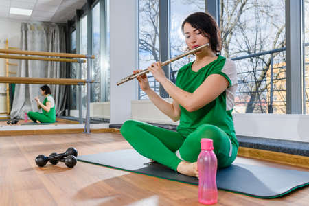 Sportive woman sit on mat in casual green outfit with dumbbells and water bottle and play on wind musical instrument indoors