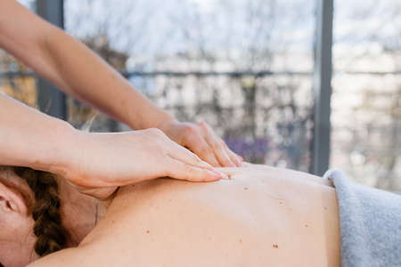 Professional spa massage concept with massagist hands on female body skin, health and body treatment indoors