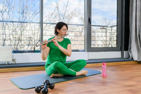 Artistic woman in green casual look sit at floor after workout and play on fife musical instrument at light studio with panoramic window