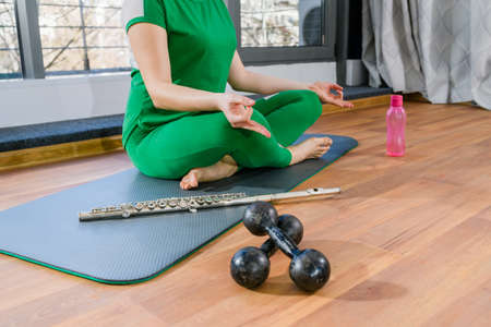 Woman with hidden face sit on sport mat in lotus yoga pose with dumbbells, water bottle and bassoon wind musical instrument