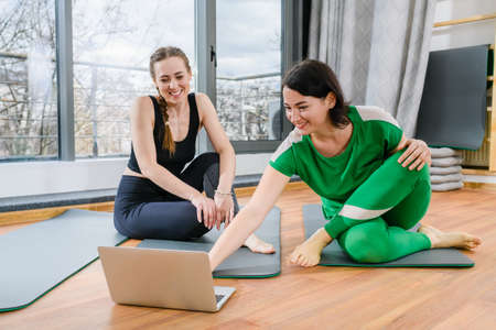 Two smiling women sit on mats with open laptop screen and prepare to exercise with online tutorials at light fitness studio Imagens