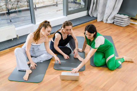 Three sportive girls sitting on mats, looking at laptop screen during online yoga fitness tutorial class Imagens