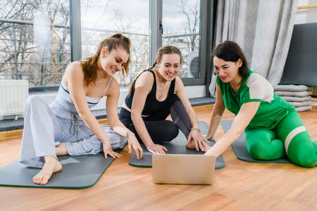 Three sportive girls sit on mats in fitness studio during online yoga exercises workout training tutorials Imagens