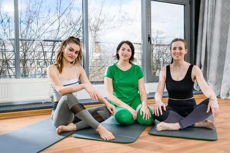 Three smiling sport women sitting on mats barefoot in light fitness studio, group workout training exercises