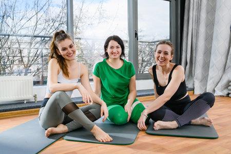 Three positive women in sportswear sit on sports mats barefoot at light fitness yoga studio, group portrait