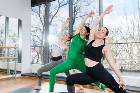 Three young women in sportswear exercise workout at light studio, stretch legs with hands up, group training