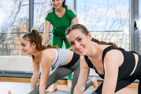 Group female stretching workout exerises with personal trainer in light gym fitness studio, sports healthy lifestyle