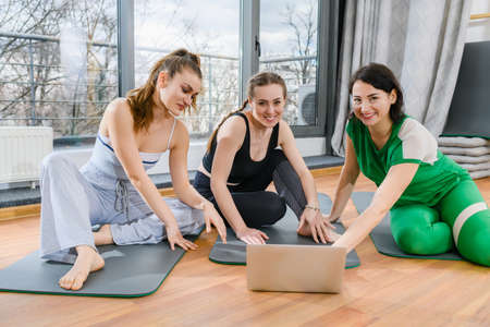 Three sportive girls sit on mats in fitness studio during online yoga exercises workout training tutorials 스톡 콘텐츠