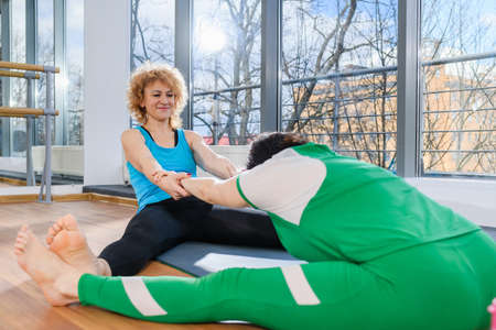 Two fit women make stretching exercises together