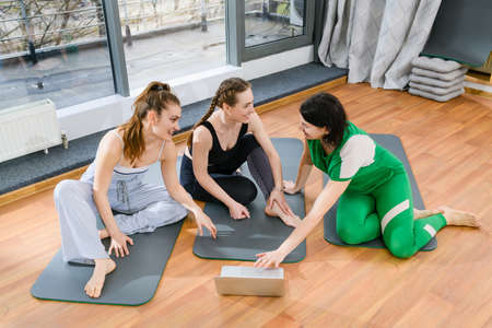 Three sportive girls sitting on mats, looking at laptop screen during online yoga fitness tutorial class 스톡 콘텐츠