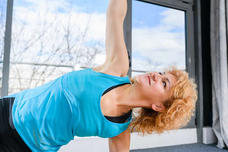 Mature positive fit woman in sportswear stand on one hand and feet toes on sports mat in light fitness studio hall